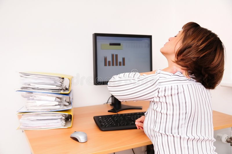 Neck pain from work. Business woman with neck pain sits on workplace with documents and monitor on table