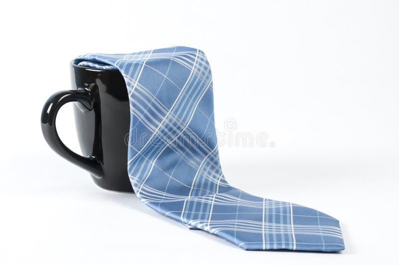 Neck tie and mug. A blue tie and a black coffee mug stock photos