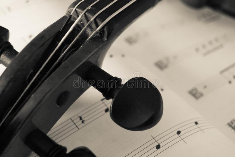 Neck of a Viola Orchestra instrument laying on music paper. Neck of a orchestra string instrument viola or violin laying on music paper royalty free stock photo