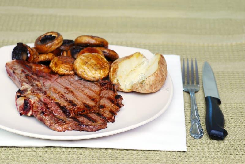 Necken Sie Steak mit Pilzen und einer gebackenen Kartoffel lizenzfreies stockfoto
