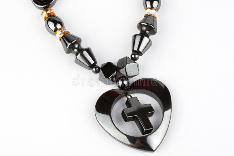 Necklace with cross in heart. Black Necklace with cross in heart on the white royalty free stock photo