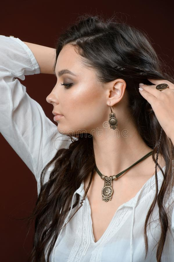 Necklace and earring on young woman. Beautiful model with perfect long hair stock photos