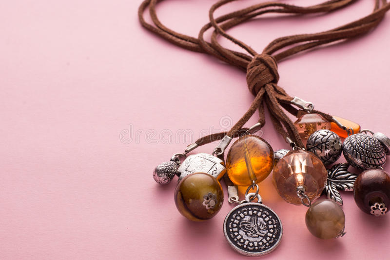 Necklace Made with Brown Leather and Silver Charms. High Angle Still Life View of Handmade Artisan Jewellery on Pink Background - Stylish and Funky Necklace Made royalty free stock photography
