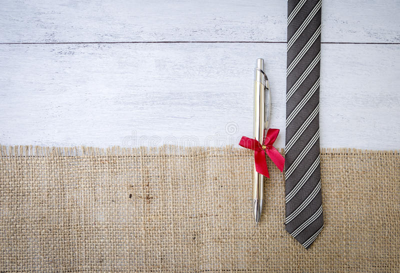 Necktie and new pen gift on hessian fabric. Father`s day concept background, necktie and new pen gift on hessian fabric over white wood background stock image