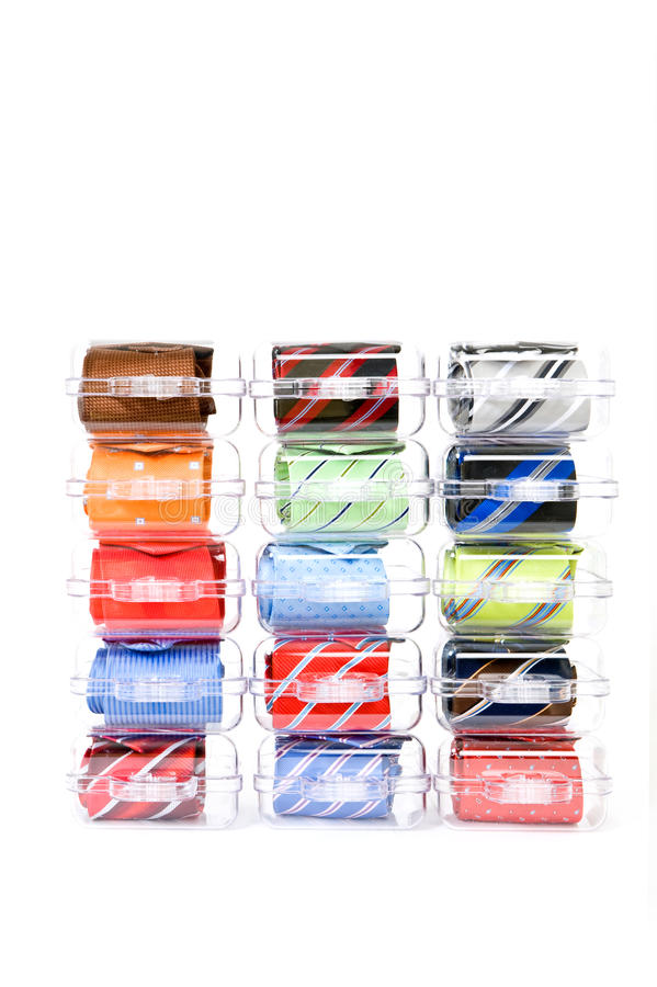 Neckties in gift boxes. Fifteen assorted neckties in various colors in gift boxes, stacked on display against a white background royalty free stock photos