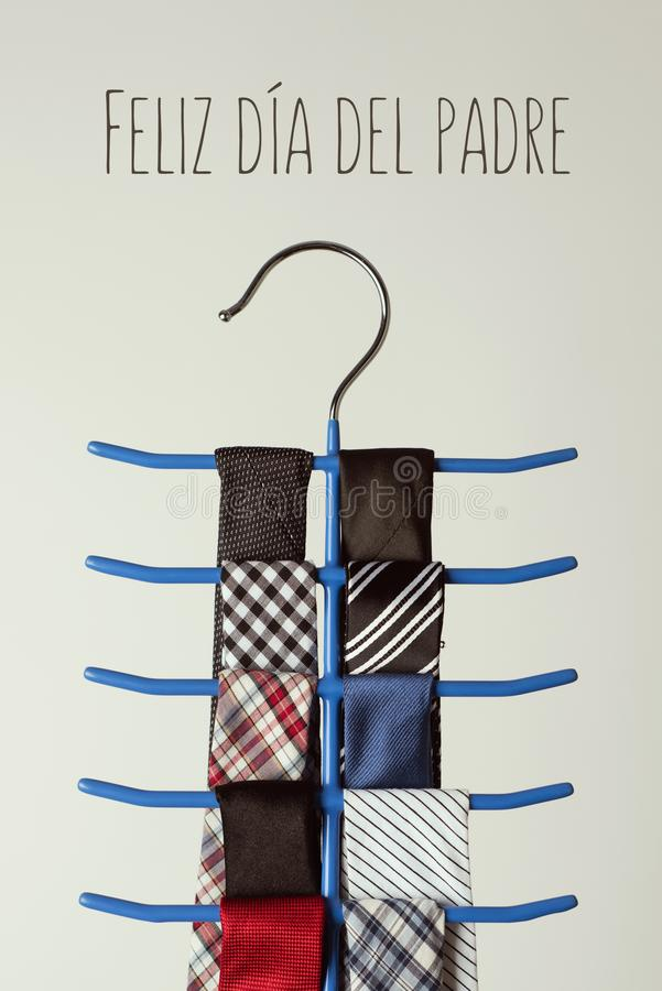 Neckties and text happy fathers day. The text feliz dia del padre, happy fathers day written in spanish, and a necktie hanger with some neckties of different stock images