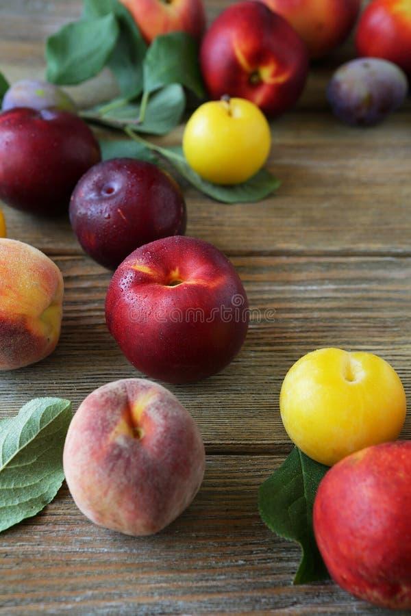 Nectarina e pêssegos no fundo de madeira foto de stock