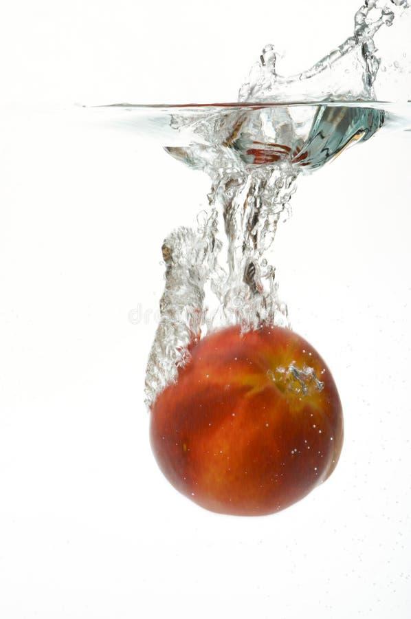 Nectarina que cae en agua imagenes de archivo