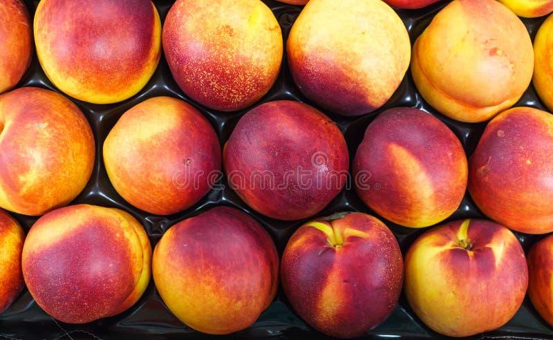 nectarina Vermelho-amarelas em uma gaveta na tabela imagem de stock