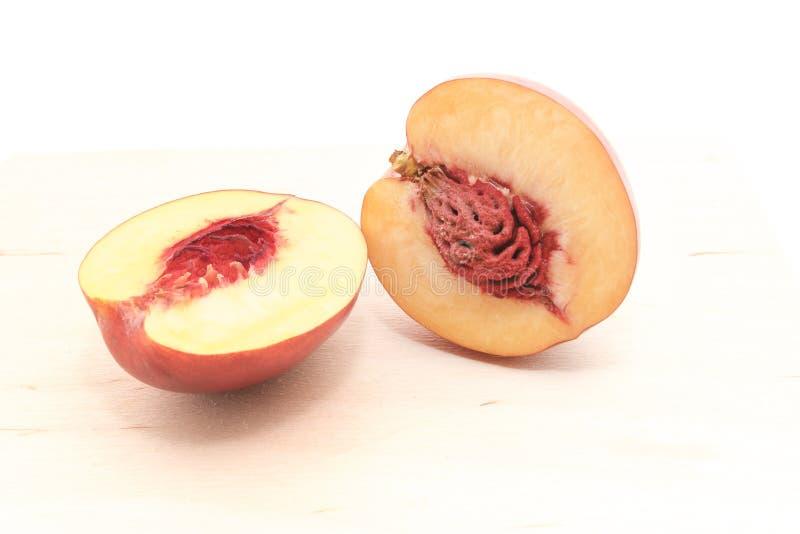 Nectarine in een besnoeiing met een been op een witte achtergrond wordt geïsoleerd die stock foto
