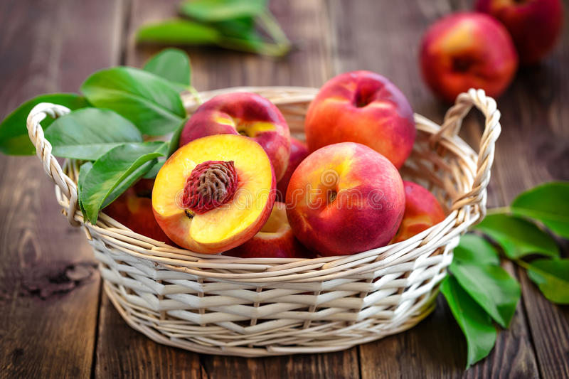 Nectarine. Fruits with leaves in a basket royalty free stock photos