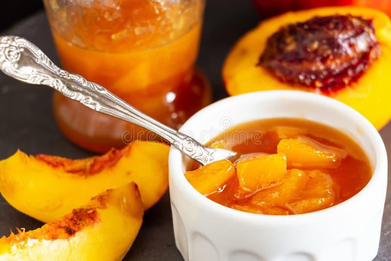 Nectarine jam confiture in ramekin and jar. Dark background. Selective focus. Close up stock photo