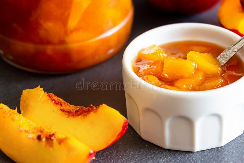Nectarine jam confiture in ramekin and jar. Dark background. Selective focus. Close up.  royalty free stock photo
