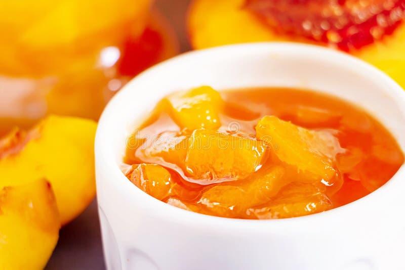Nectarine jam in ramekin. Dark background. Selective focus. Close up. Breakfast concept royalty free stock images