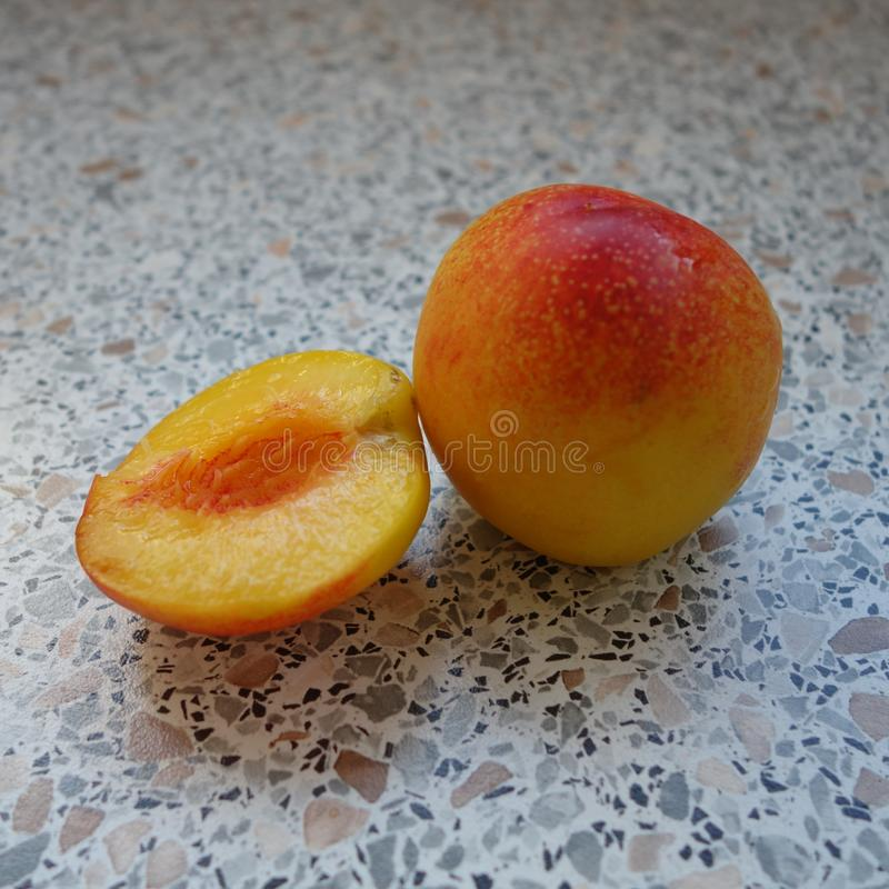 Nectarine lying on the table. A nectarine and a slice of nectarine royalty free stock photos