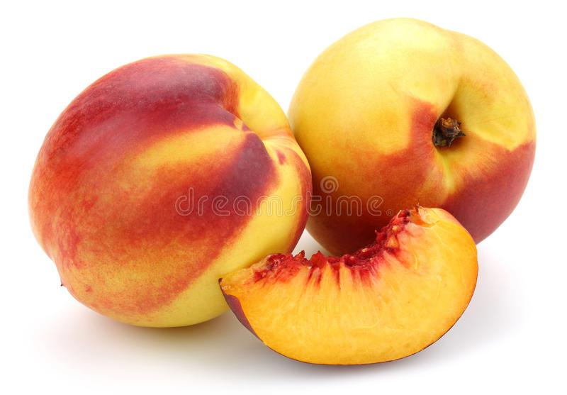 Nectarine peaches with slice on white background. Nectarine peaches with slice isolated on white background royalty free stock images