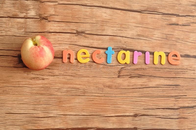 A nectarine with the word nectarine. On a wooden table stock photos