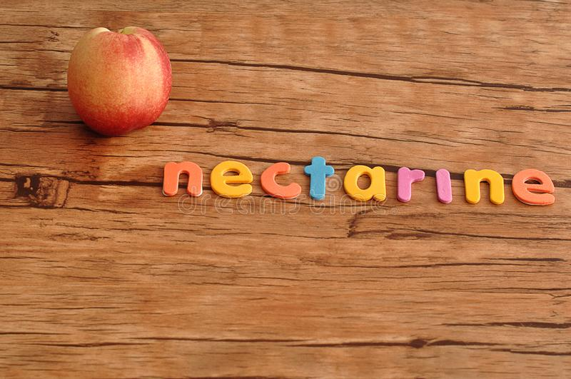 A nectarine with the word nectarine. On a wooden table stock image