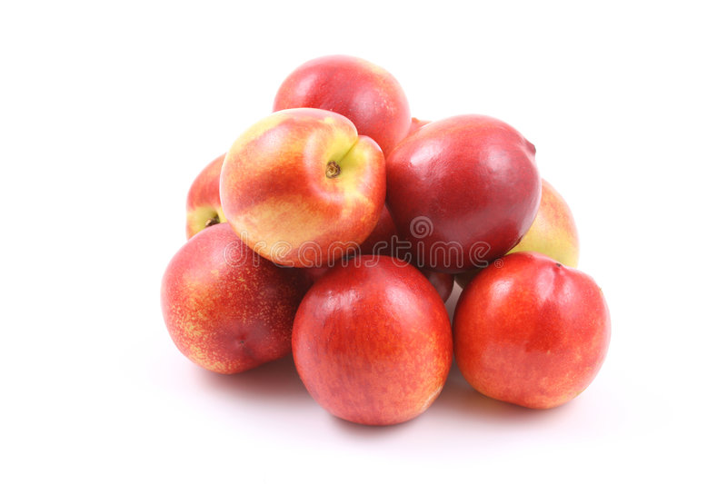Nectarines. Pile of fresh and delicious nectarines isolated on white royalty free stock images