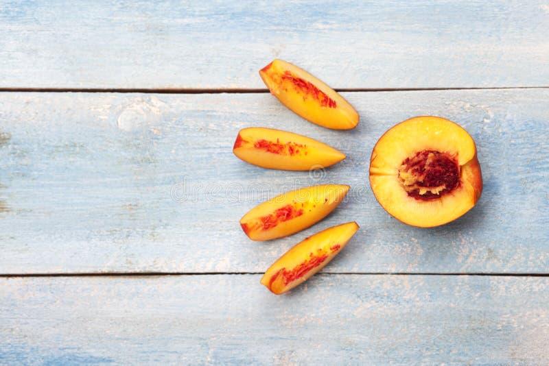 Nectarines coupées en tranches fraîches sur la table en bois bleue images stock