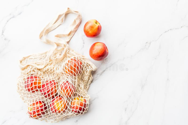 Nectarines crues fraîches se situant dans le sac de ficelle sur le fond de marbre blanc Configuration plate, ?t? de vue sup?rieur images stock