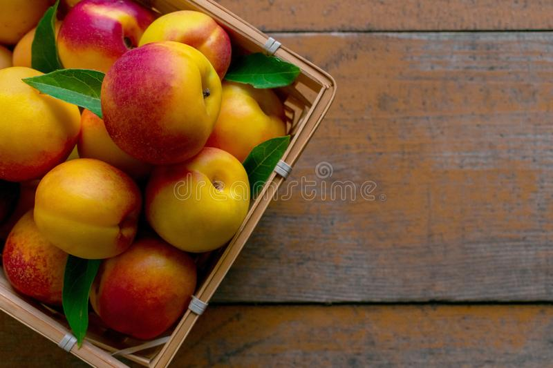 Nectarines with leaves on a wooden background. Summer fruits. Food photo. View from above stock photo