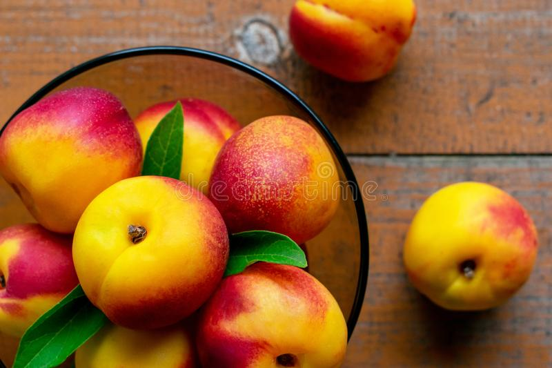 Nectarines with leaves on a wooden background. Summer fruits. Food photo. View from above stock photos