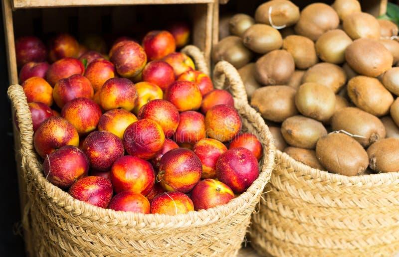 Nectarines mûres dans les paniers en osier sur le compteur photographie stock