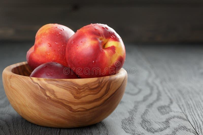 Nectarines in olijf houten kom op eiken lijst royalty-vrije stock fotografie