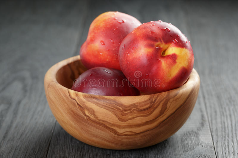 Nectarines in olijf houten kom op eiken lijst stock foto