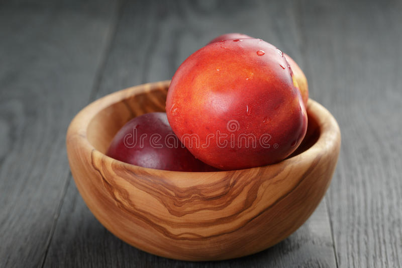 Nectarines in olijf houten kom op eiken lijst stock afbeeldingen