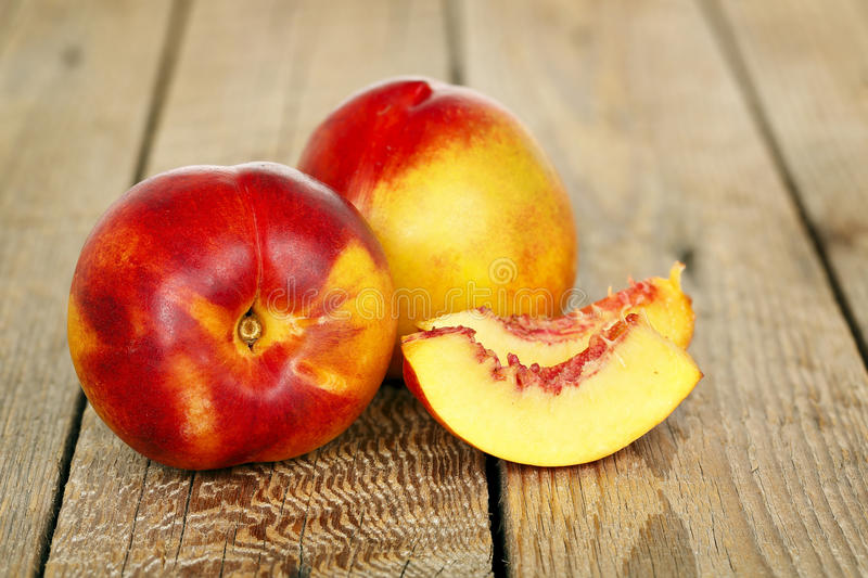 Nectarines. With slices on wooden background royalty free stock images