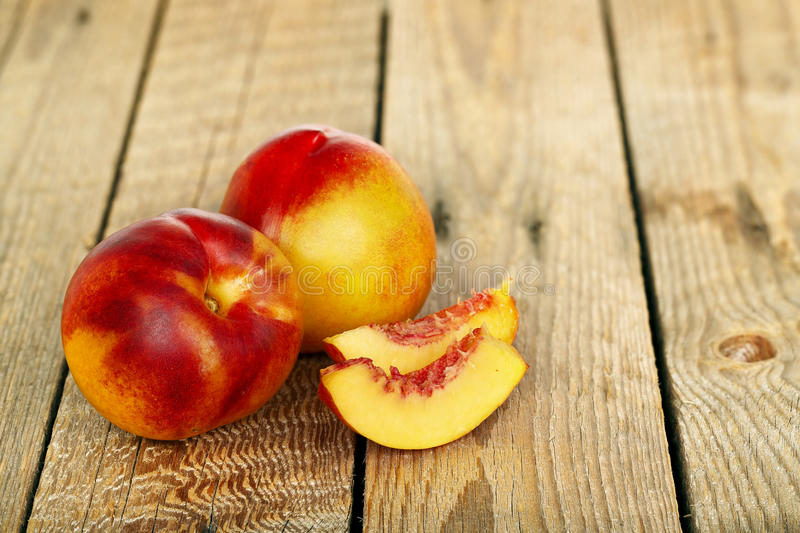 Nectarines. With slices on wooden background royalty free stock photo