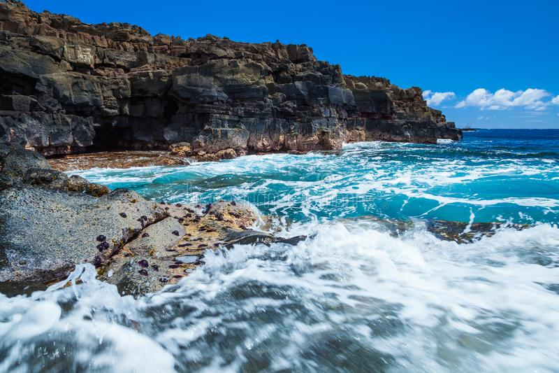 Nedanför Hawaii Lava Rock Sea Cliffs och in i havgrottorna royaltyfri foto