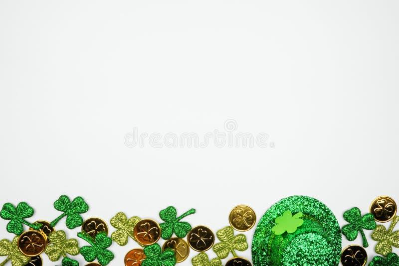 Nederkant på St Patricks Day mot en vit bakgrund, toppvy med guldmynt, schampo och leprechaun-hatt royaltyfria bilder