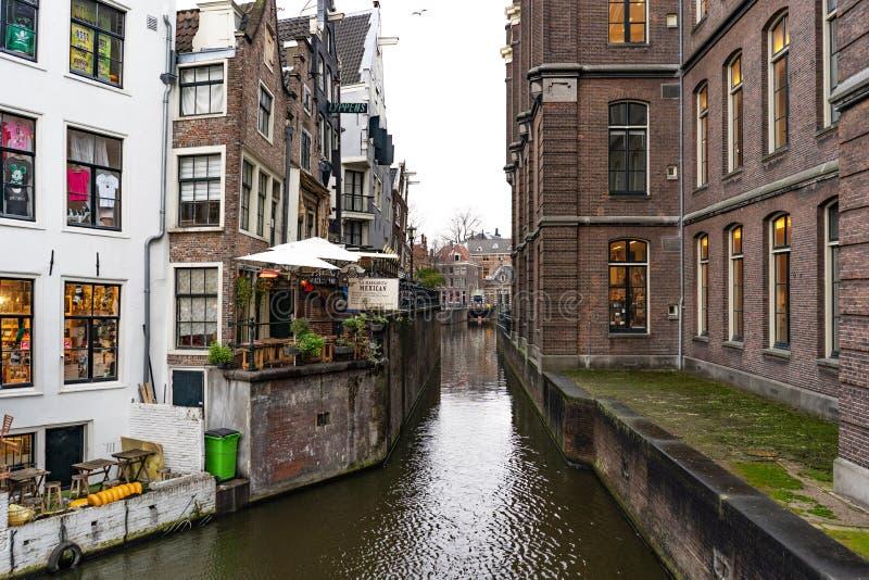 Nederländerna Amsterdam - December 19 2018: smal kanal och byggnader i amsterdam, Nederländerna arkivbilder
