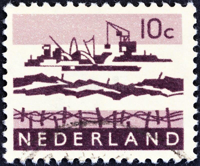 NEDERLÄNDERNA - CIRCA 1963: En stämpel som skrivs ut i Nederländerna, visar deltautgrävningarbeten, circa 1963 royaltyfria bilder