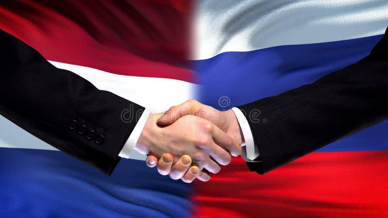 Nederländerna- och Ryssland handskakning, internationellt kamratskap, flaggabakgrund arkivfoto