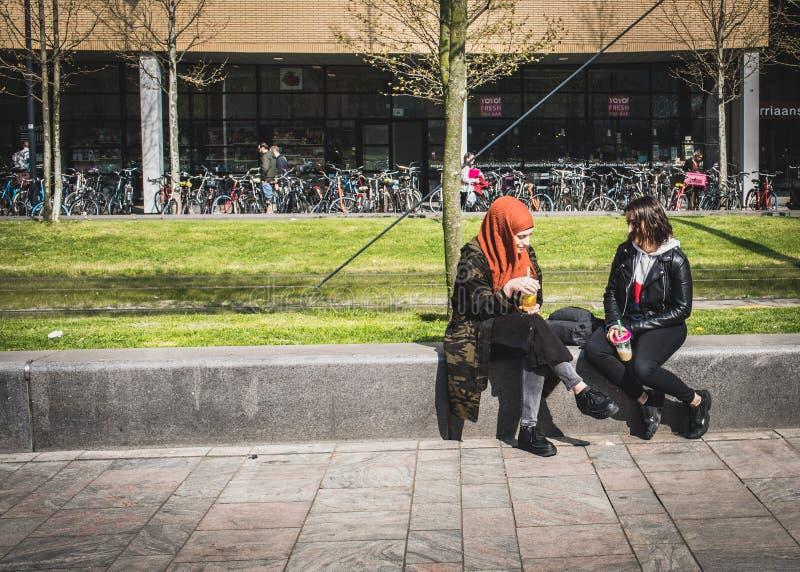 NEDERLÄNDSKA ROTTERDAM - - APRIL, 15, 2019: Två flickor sitter och dricka nya smoothies i centret Rotterdam royaltyfri foto