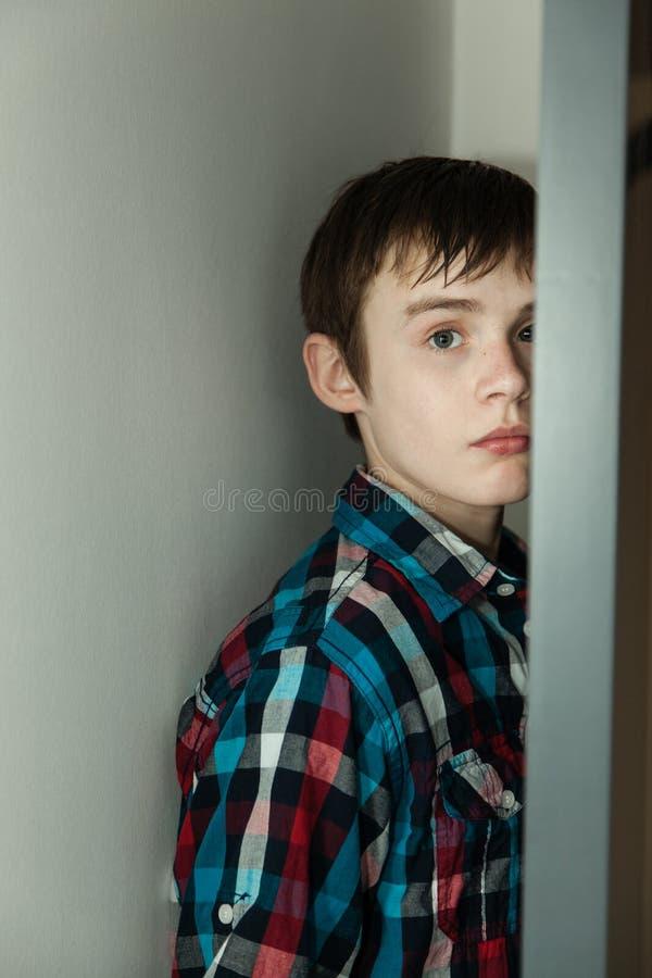 Nederlag för tonårs- pojke bak öppen dörr i hem royaltyfri fotografi