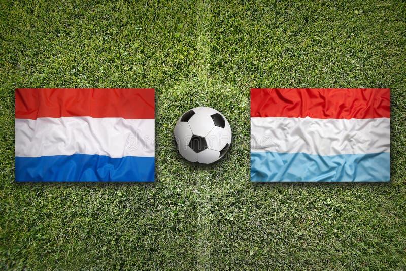 Nederland versus De vlaggen van Luxemburg op voetbalgebied stock fotografie