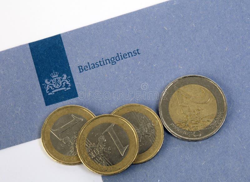 Nederlandse blauwe belastingsenvelop van de belastingdienst met euro muntstukken royalty-vrije stock afbeelding