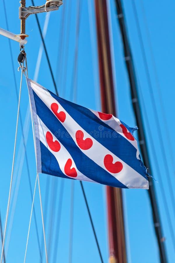 Nederlandse Frisian-vlag op een varend schip stock afbeeldingen
