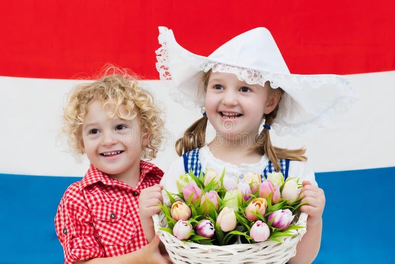 Nederlandse jonge geitjes met van tulpenbloemen en Nederland vlag royalty-vrije stock fotografie