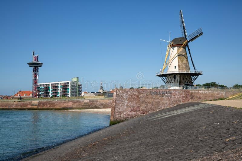 Nederlandse traditionele windmolen bij dijk dichtbij stad Vlissingen stock afbeeldingen