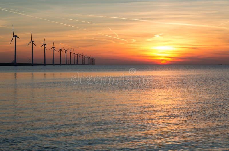 Nederlandse voor de kust windturbines tijdens een zonsondergang stock fotografie