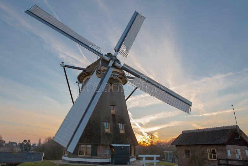 Nederlandse windmolen bij de zonsondergang stock foto's