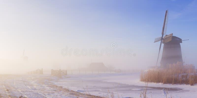 Nederlandse windmolen in een mistig de winterlandschap in de ochtend royalty-vrije stock foto