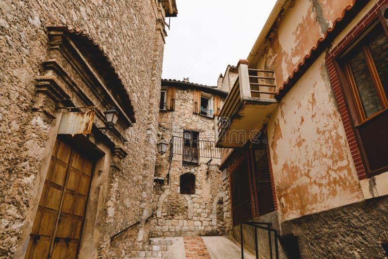 nedersta sikt av den smala gatan med forntida byggnader på den gamla staden, Peille, Frankrike royaltyfri bild