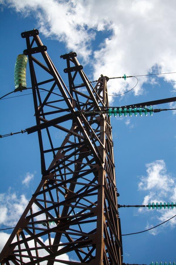 Nedersta sikt av en metallpol av en kraftledning med en mängd av elektriska trådar mot en blå molnig himmel royaltyfri foto
